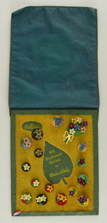 "Upright rectangular card covered in a green felt and cut out of leaf with straw-like material. A green felt border along the edge. 15 circular buttons in green, black, peach, yellow red and blue of various sizes attached to board, with flowers on each button.  Attached is also a brooch of a bouquet of flowers. printed on upper left corner La Mode [logo]; printed in center of leaf ""Old Fashioned Garden""/ ""by Marion Weeber"""