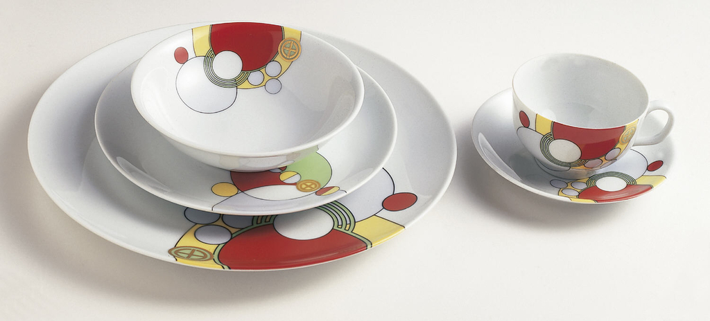 """Hemispherical cup with plain loop handle; exterior decorated with abstract enamel decal with pattern of interlocking circles in red, pale blue, yellow and green, all outlined in black. Gilded """"mon"""" insignia over circle decoration at one side."""