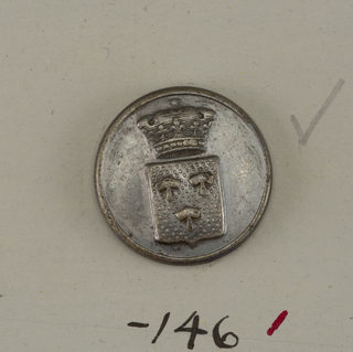 Flat button with ornament showing a shield with heraldic devices under a crown. Brass back and shank.  On card E