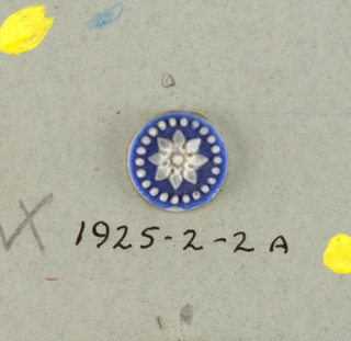 Medallions in style of Wedgwood Jasperware, twelve petaled white flowers on blue ground. Central hole indicates they may have been intended for buttons.