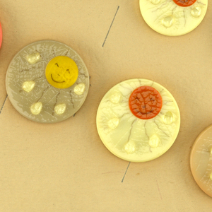 """Upright rectangular biege card with yellow boarder around edges; 18 circular yellow, green and orange buttons of various sizes sewn on face, each button a smiling sun with rain drops.  printed in upper left corner of card: La Mode [logo], presents """"April Showers""""/ """"designed by Marion Weeber Welsh"""""""