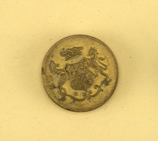 Flat button with ornament showing coat of arms on a shield; supporters, a lion and a fabulous beast; crown. Brass back and shank.  On card C