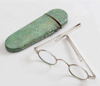 Oblong green stained case (a) with glasses (b) with silver plated oval rims and straight temple pieces hinged near mid-pint to fold.