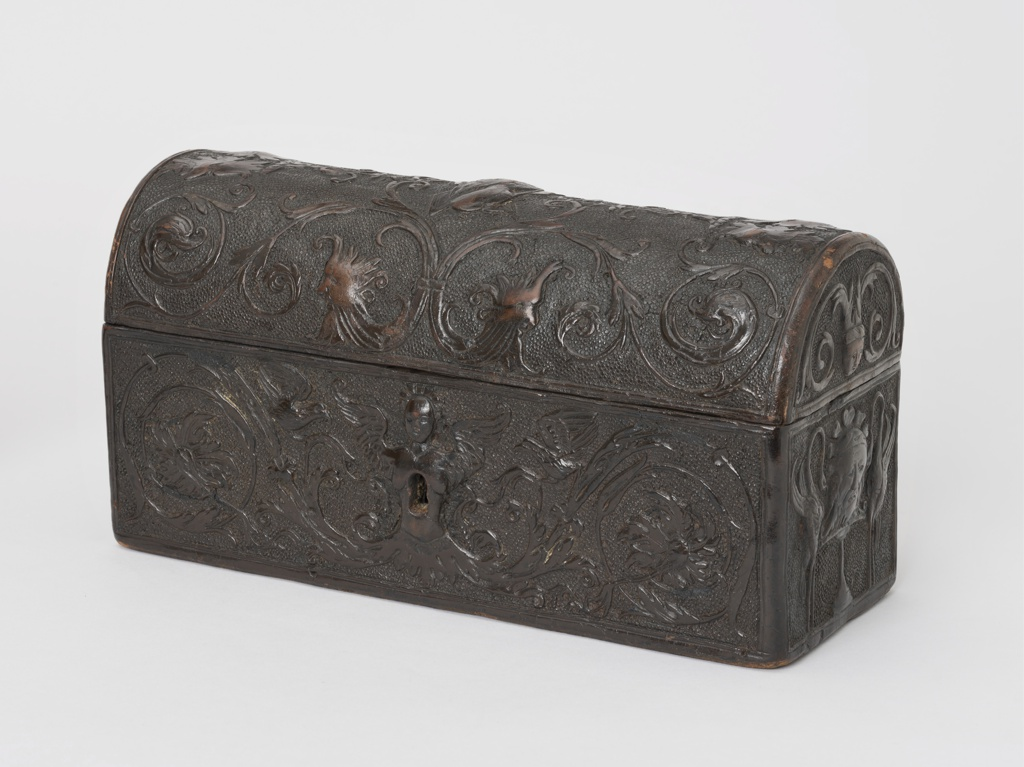 A casket-shaped wood box, fitted with iron lock, made of tooled leather in Renaissance design showing masks, and foliated scrolls with bird-like animals, decorated with large curves. Inside lining of brown silk taffeta with embroidery in green and brown silk showing trees, leaves, and architecture. On the front, bird-like animals are designed within the scrolling pattern.