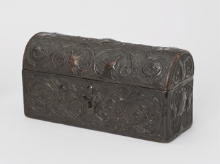 Casket-shaped box, fitted with iron lock, made of tooled leather over wood;  surface design showing Renaissance style masks, and foliated scrolls with bird-like animals, decorated with large curves. Inside lining of brown silk taffeta with embroidery in green and brown silk showing trees, leaves, and architecture.