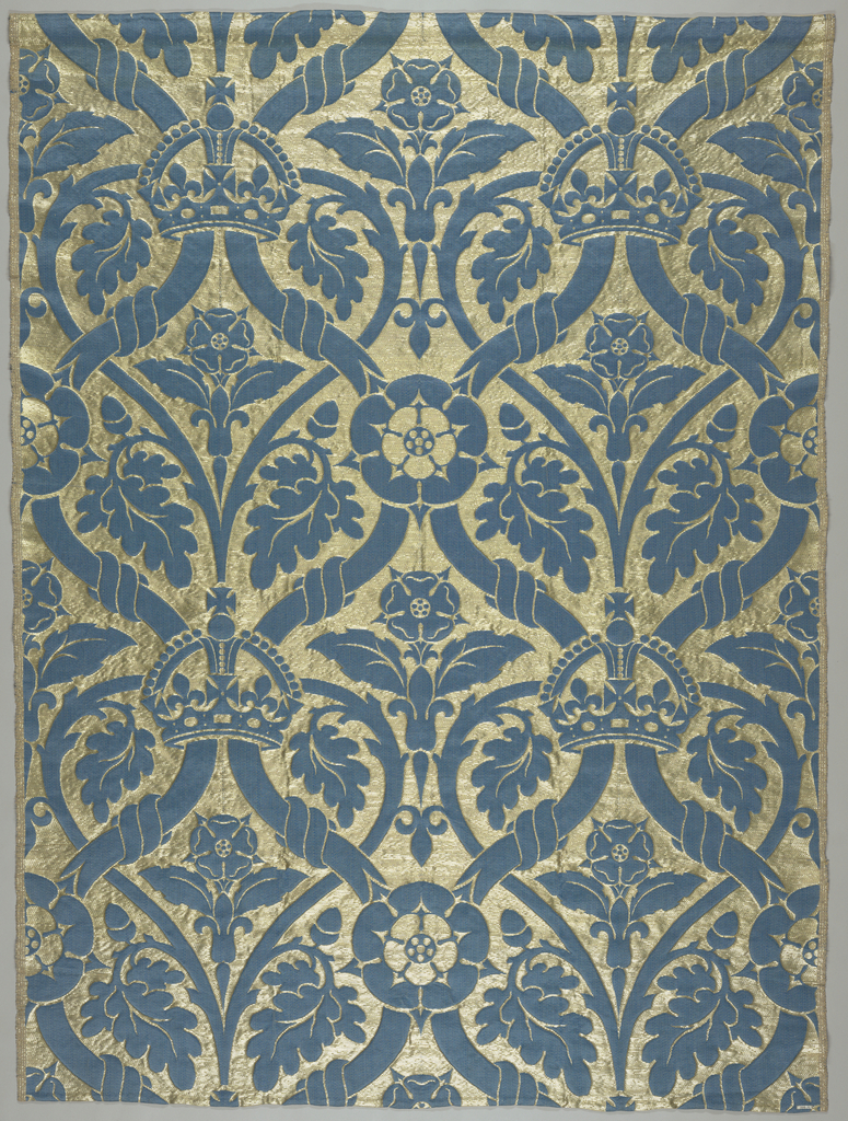 Sample of fabric used at Coronation of King George VI and Elizabeth of England, May 12, 1937. Gold background formed by extra wefts of one flat strip of gilt tinsel and three wefts of gold-colored silk. Design in blue mercerized cotton in satin weave. Great swinging bands form ogives with crown at lower point and Tudor rose at upper point. Each ogive encloses a stiffly symmetrical arrangement of central stem, fleurs-de-lys, and oak leaves, topped by Tudor rose. Extra warp of gold-colored silk ties down the gold wefts in twill with diagonals running from lower right to upper left. Functional weft of unbleached linen (?). Both selvages present.
