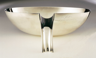 A silver sauce boat with a hollow handle off the side.