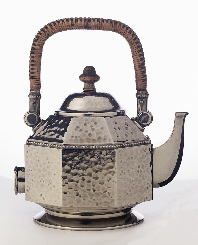 Eight-sided teapot with small, separate domed lid, all of plated metal with a hammered texture; curved tapering spout on one side, circular outlet for electrical plug on opposite side; on smooth circular foot; inverted U-shaped wooden handle rapped in rattan at top; wood knob on lid.