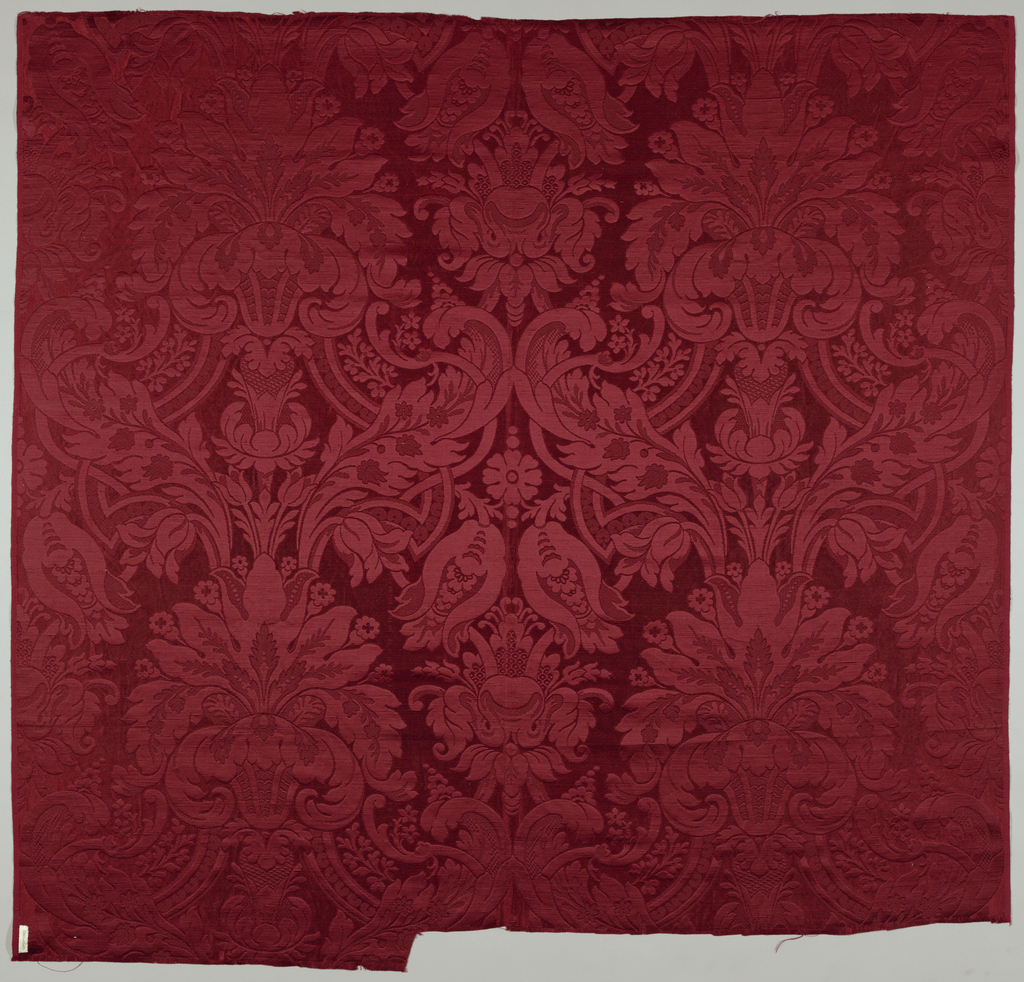 Satin and twill weave in heavy red silk; large scale symmetrical pattern, double width, of palmette and foliage. Machine woven adaptation of 17th century damask pattern.