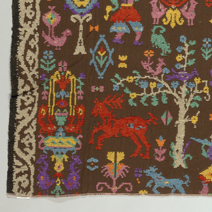 Fabric designed by Alexander Morton, inspired by Sardinian peasant embroideries. Design of falconers on horseback, reindeer, hunters, flowering trees, etc., in brilliant polychrome chenille yarns on a dark brown cotton ground, with white floral vine borders on each selvedge edge and down the center.