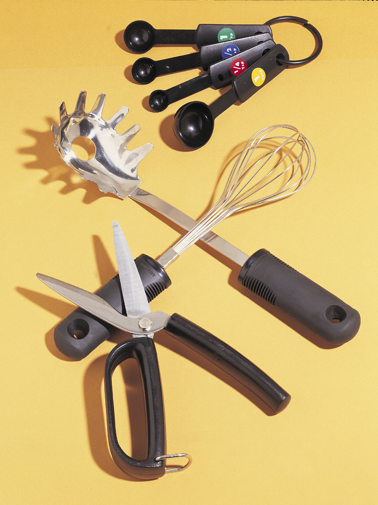 One of a set of kitchen utensils with wide, ridged handles of thermoplastic and ABS plastic, ergonomically designed.