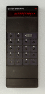 "Black rectangular calculator with small round buttons in sunken squares, white letters and numbers. Above, red screen and in white: ""Sinclair Executive."""
