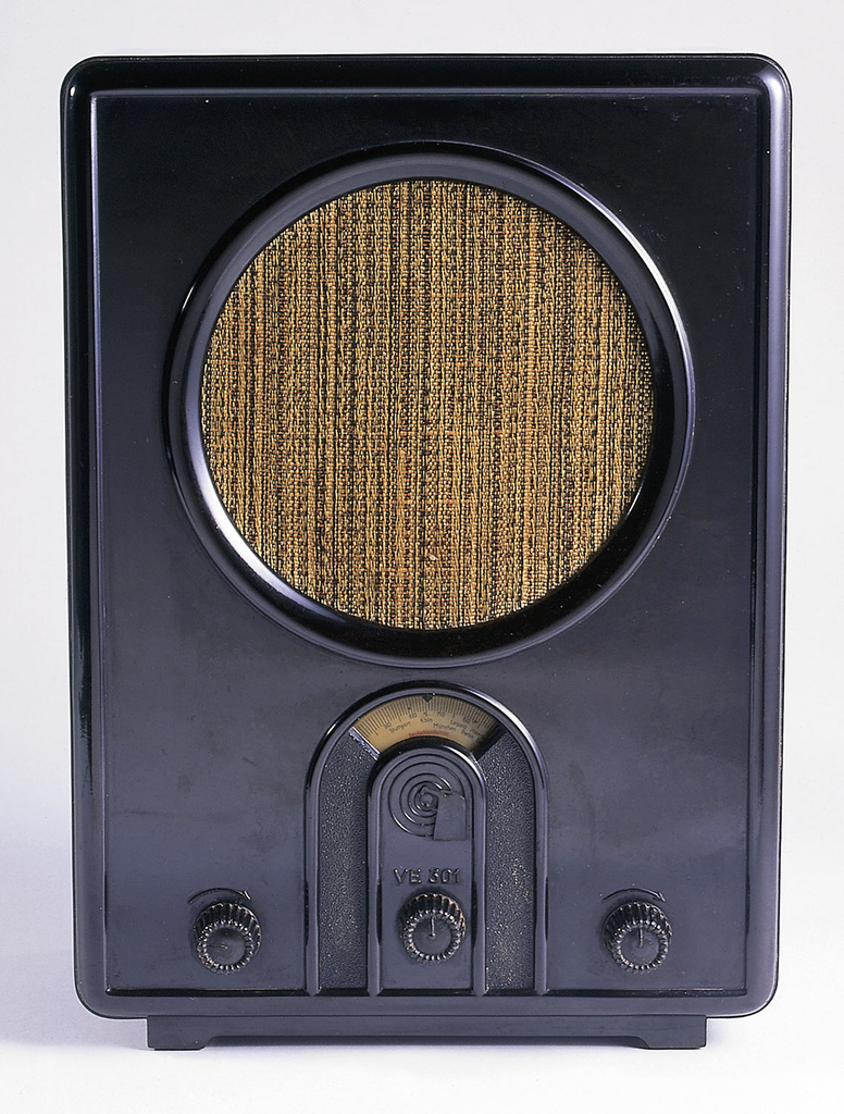 Rectangular black Bakelite case with a slightly smaller foot; large circular speaker on front covered with brown and black woven fabric. Below speaker is an arch-shaped station indicator above three small circular dials.