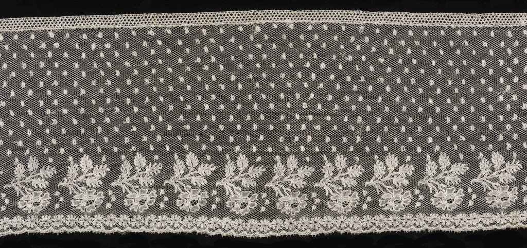 Straight border of Mechlin lace with a design of small square ornaments sprinkled over field has border of detached motifs of flower and leaves above row of flowerheads.