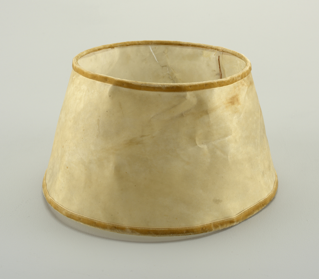Slightly conical beige lampshade with golden-yellow velvet band along top and bottom edges.
