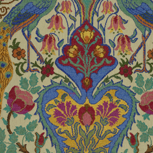 Fabric designed by Alexander Morton, inspired by Sardinian peasant embroideries. Large scale symmetrical design with a central urn flanked by peacocks, gazelles, and flowering trees. Brocaded in brilliant polychrome chenille yarns on a beige cotton ground.