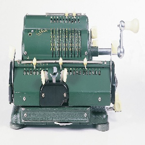Dark green metal housing with off-white plastic buttons and handles. Upper part consists of slightly rounded top with mechanics. Lower part has two handles on right nad left side. Bottom metal platform supported by buttons.