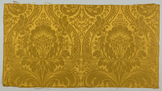 Curving strapwork containing large leaves.  Gold color.