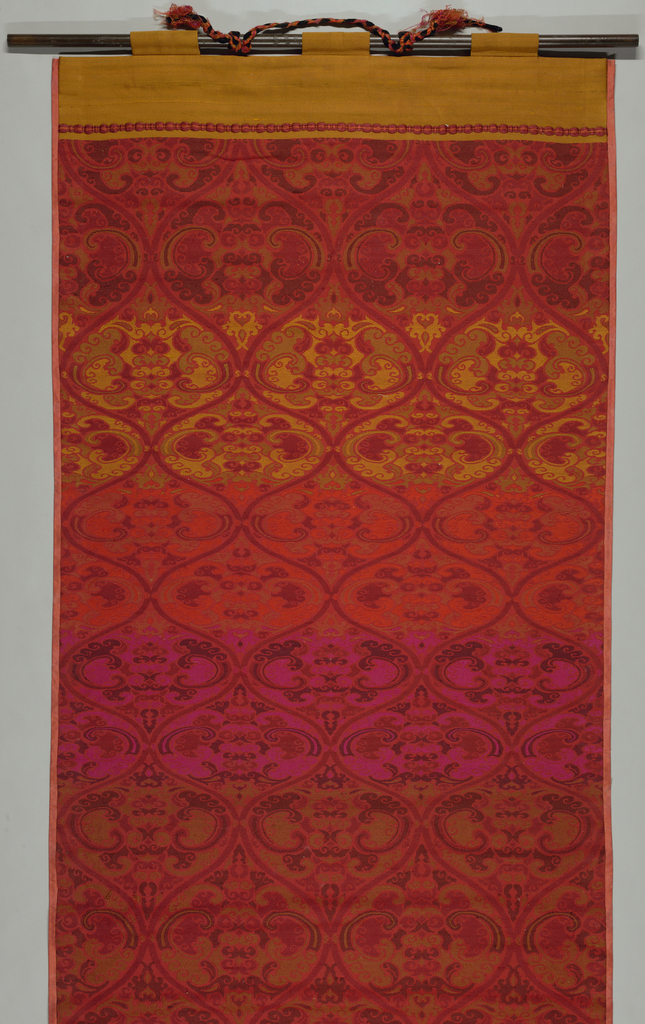 Hanging in tones of red, magenta and orange has ogival forms filled with a scrolling vine pattern. Top section has a solid orange band, and bottom section has a wider red band.