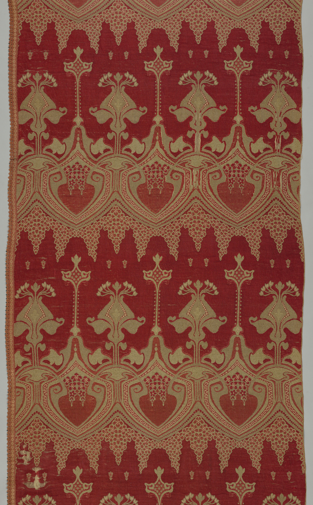 Large-scale Art Nouveau design of highly stylized floral forms suggesting lilies rise from between shield-shaped forms that frame pomegranate shapes. These are outlined in a narrow Greek fret. In red and gray.