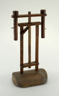 Wooden base with curved corners, thinner on one side. Two wood supports imbedded in base, a depression between them from the notched and adjustable center ratchet. At top, two suspended wooden sockets attached to a cross beam with peg construction.