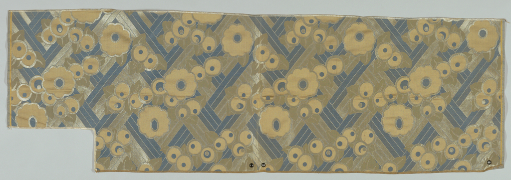 Designs for airline upholstery. Component A is a design of flattened flowers on an abstracted diamond grid. Gold, off-white and blue. Grommets at top. Irregular shape. Component B is the source for A with the same design but 1/12 the size in gold, grey, beige and two blues.