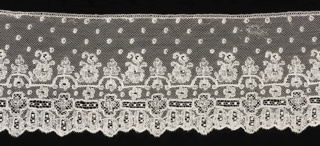 Mechlin border with the upper part showing floral sprays and leaf ornaments with little squares sprinkled over the field. The lower part has an openwork band with medallions and a scalloped border of pendant flowers.