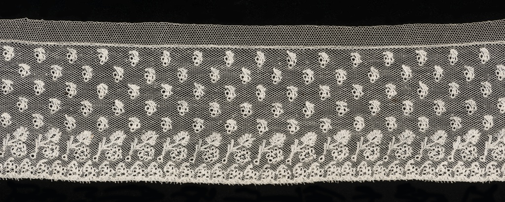 Straight border of Mechlin lace with a design of small bud ornaments sprinkled over the field. Bottom border has detached flower and leaf motifs above a row of flowers.