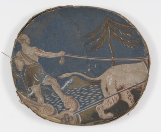 Pasteboard bandbox lid covered with wallpaper: blue background, male figure standing in chariot drawn by lion (only back part of lion visible) in beiges, browns. Rim: blue black ground, three lines of small blue dots, one line of large white and pink dots.
