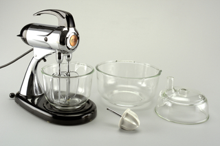 "One-piece, metal and plastic mixer stand (a) composed of cylindrical, metal motor unit with plastic handle at top and settings dial on rear, atop a curved metal arm on a tear-drop shaped plastic base with name on side: ""Sunbeam / MIXMASTER""; circular plastic turntable (b) inset in base, to support one of two interchangeable bowls: small circular clear glass bowl (c); large circular clear glass bowl (d).  Motor unit tilts back, allowing removal of bowl, and access to two detachable metal beaters (e,f) descending from unit.  Additional interchangeable components are: white ceramic reamer on metal shaft (g); clear glass juicer (h) in form of shallow, circular bowl with tube-like protrusion."