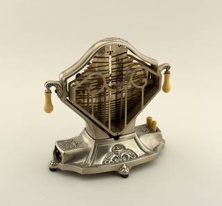 An early metal toaster in a diamond shape with a visible heating elements and metal frames to hold the toast on either side.  Roughly rectangular cast metal base with small decorative floral designs near the feet; two cylindrical buttons on one side. Small pendant knobs on opposite sides of toaster.