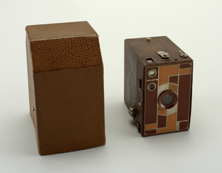 Box camera (a) covered in brown leatherette; metal faceplate enameled with tan and brown geometric design.  Camera slides into box shaped leatherette-covered case (b).