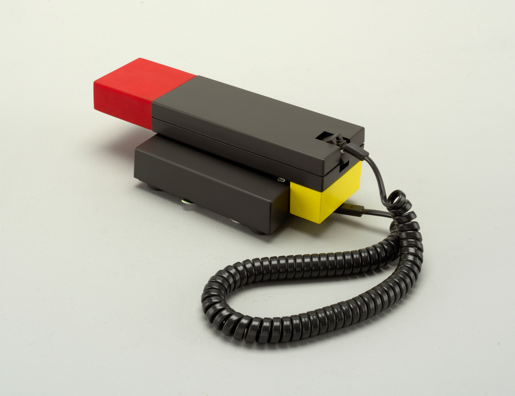 Body of grey, yellow and red rectangular components; coiled gray cord connecting handset to base.