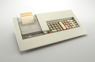 Rectangular grey adding machine. Sloping front with multipurpose keyboard. Functions of the keys are indicated by different colored areas: grey, red, orange, blue, yellow; paper roll attached to the back of the machine on left side.