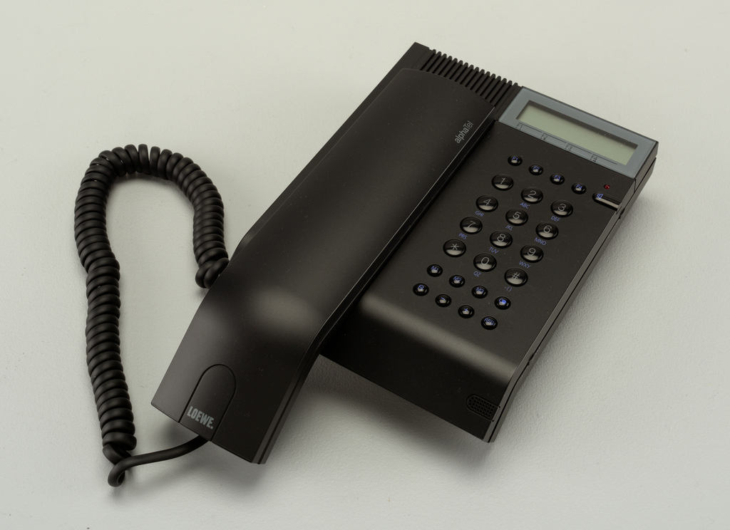 Black rectangular body with digital readout and keypad on right, rectangular handset and cord on left.