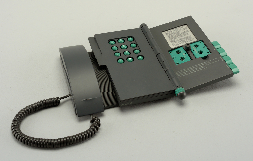 A black telephone connected to rectangle keypad with a hinge on its right side holding open a phone book area.