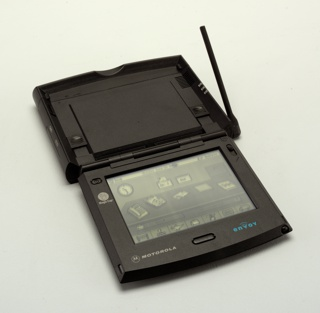 Dark gray rectangular form with antenna on right side, and hinged at the top; the lid lifts to reveal a rectangular screen showing icons for various functions.