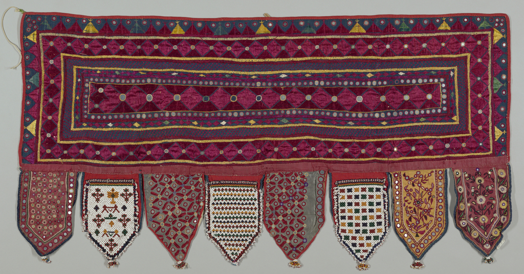 Hanging in the shape of a horizontal rectangle with eight tabs at the bottom. The rectangle is of blue cotton plain weave with embroidery in red and yellow silk in borders ornamented with discs of mirrored glass. Five tabs are of this type of embroidery and three are beadwork.