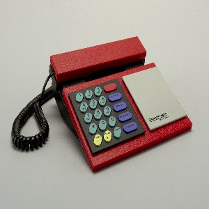 """Red and black housing with flat rectangular face having square black panel on left with oval number and function keys in green, purple, yellow and red; light gray panel on right, with """"Copenhagen / Bang & Olufsen"""" logo at bottom. Oblong, flat red handset  sits horizontally in cradle above key and logo panels. Spiral black cord connects handset to housing."""