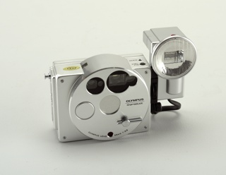 """Aluminum body (a) of rectangular form with circular panel set slightly to right of center front. Panel has circular lens opening in center with retractable barrier; view finder, auto-focus windows and light sensor arrays above lens;  circular shutter button to left and lever-like """"barrier knob"""" at lower right.  Body has small rewind and timer buttons on top right and battery compartment cover (b) on underside. Rectangular flash unit (c) with circular lens and short cord attaches to right side of body using screw-mount."""