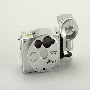 "Aluminum body (a) of rectangular form with circular panel set slightly to right of center front. Panel has circular lens opening in center with retractable barrier; view finder, auto-focus windows and light sensor arrays above lens;  circular shutter button to left and lever-like ""barrier knob"" at lower right.  Body has small rewind and timer buttons on top right and battery compartment cover (b) on underside. Rectangular flash unit (c) with circular lens and short cord attaches to right side of body using screw-mount."