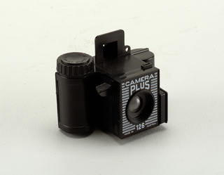 Small black plastic pocket camera for 126 pocket film. Square, box-shaped center with lens in center front. Push button on right, container for flash on left. Small window on top of center (no glass in it), winding knob on left container of the (removable) film. Sticker on back of the camera with details on Fuji Film 126.