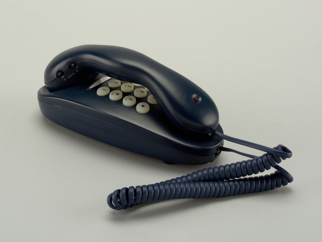 Teal oval body with white keypad buttons; shaped teal handset with circularLED indicator light on top of lower end, handset rests on body over key pad; teal cord.