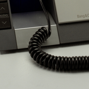 Telephone consisting of blue, angled handset, resting upright in triangular gray plastic base with function buttons on left, light gray panel on right. black coiled cord at bottom of hand set.
