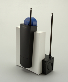 Upright rectangular white plastic base unit with antenna, on which rests the handset of blue and black plastic with antenna; power cord with plug attached to base unit.