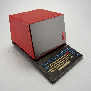 Terminal comprising integrated screen and keyboard. The flat rectangular screen set in a bright red box-shaped housing on a flat dark grey base; three red function buttons alligned vertically at bottom right of screen.  The keyboard set into base in front of the screen, with tan keys and blue, red and green function buttons.