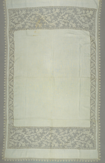 White cover with broad bands of net at each end with a needlework pattern in white of leaf forms and scrolls. Narrower band at the sides in a similar design. Edged with fine scalloped bobbin lace.