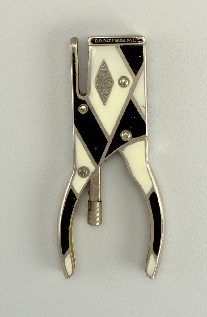 Narrow, rectilinear stapler with curved hand grips; sides decorated with overall geometric black and white enameled pattern.
