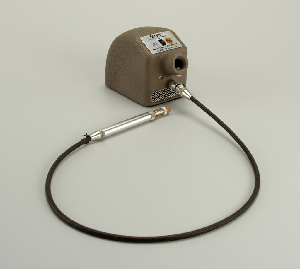 Brown, boxy metal unit housing electric motor, having short tubular projection at front with black cord below; pen-like 'wand' with pink eraser feed at end of cord.