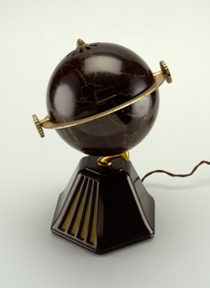 Brown Bakelite globe on six-sided brown Bakelite base. Continents, map grid, and continent and ocean names picked out in gold; gold-tone volume and tuning dials mounted on equator-like metal band encircling globe; small retangular station number read-out in center; gold-tone terminals at north and south pole positions. Two sides of base with vertical slits and fabric for speakers. Fabric-covered cord.